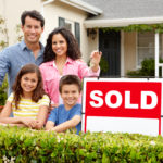 Hispanic family standing outside home smiling with sold sign