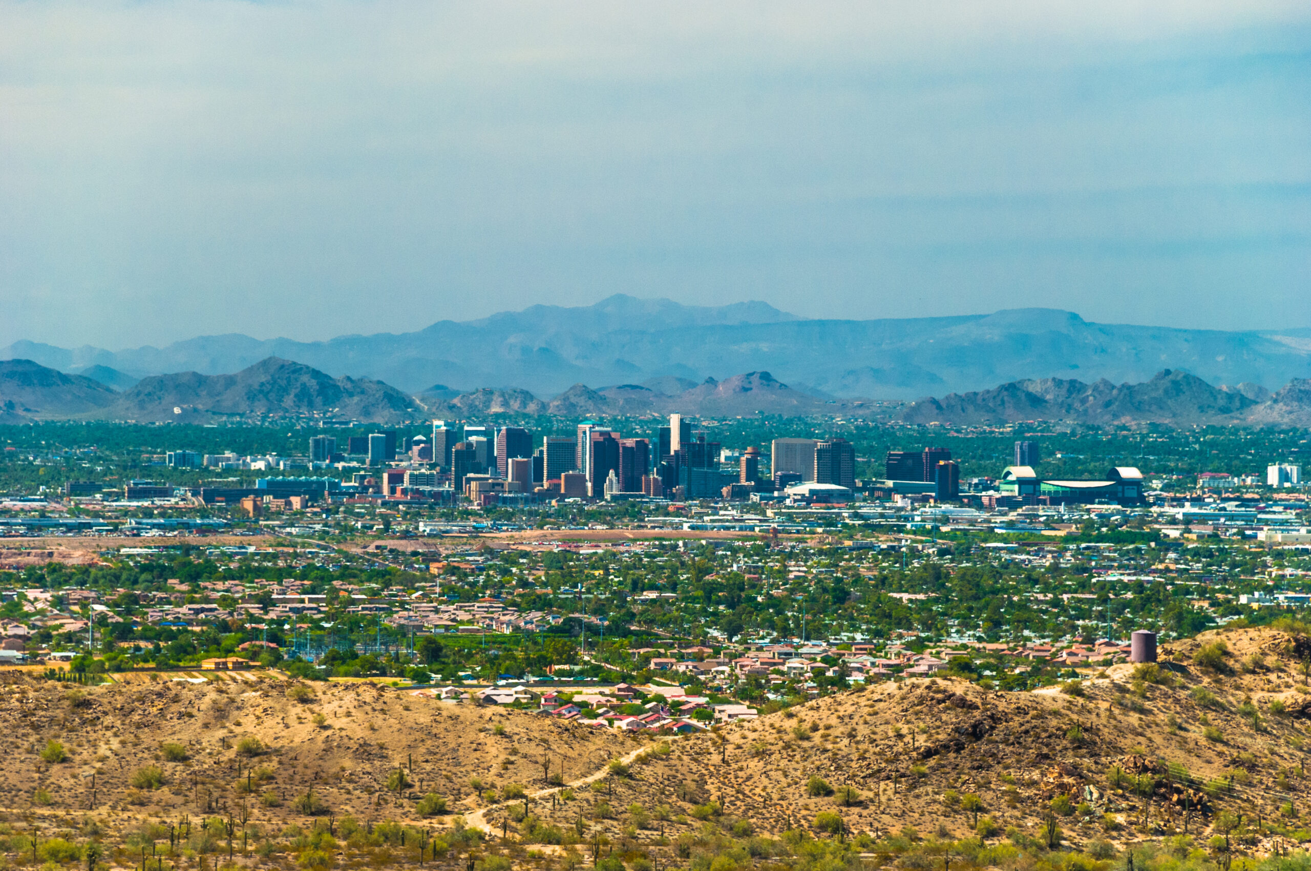 Downtown Phoenix aerial, with mountains in the far background and a desert mountain with Saguaro cactuses in the foreground.