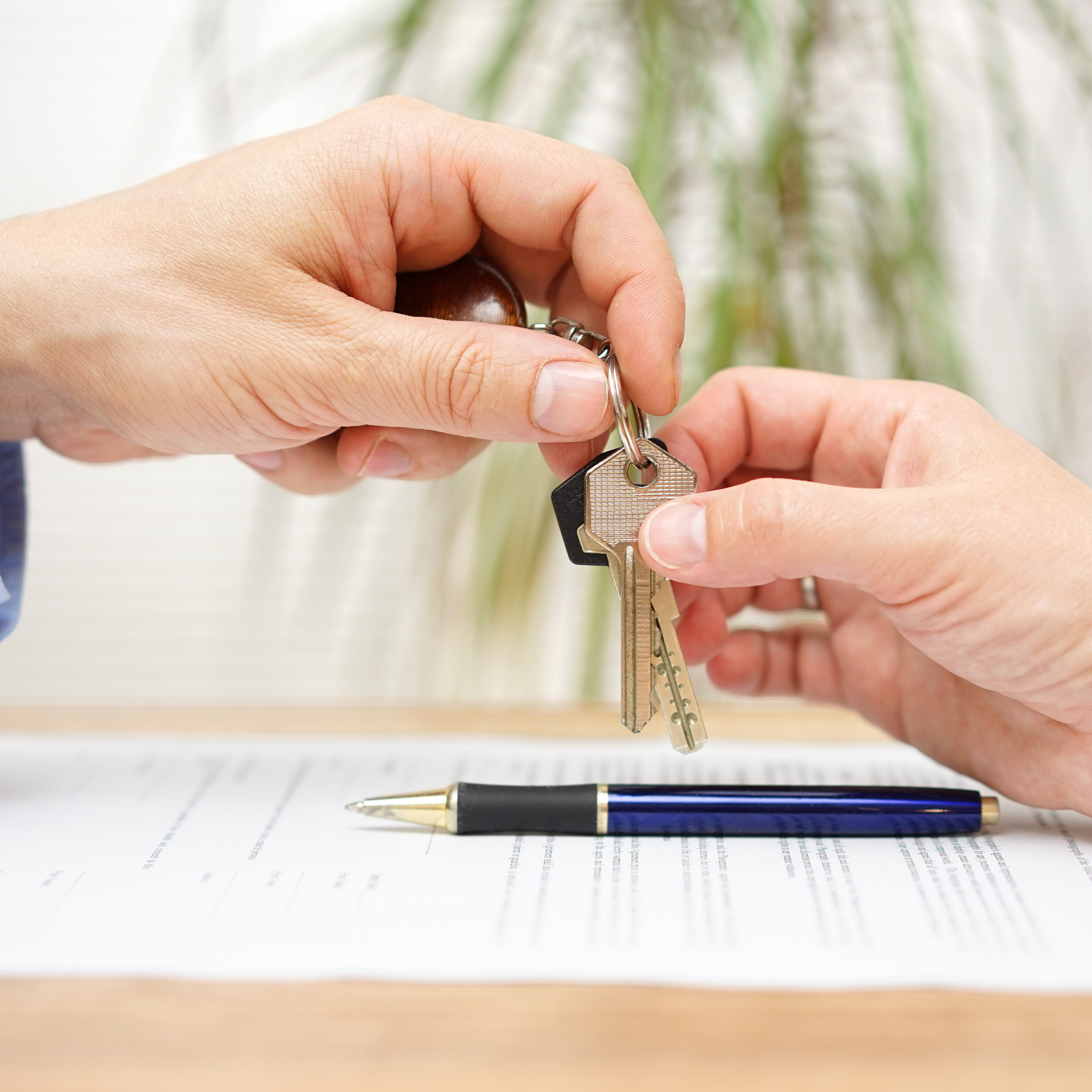 real estate agent gives house keys to his client after signing contract